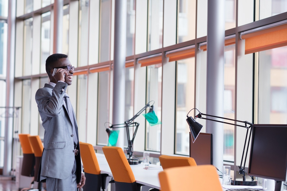 Happy smiling successful African American businessman  in a suit in a modern bright office indoors speel on phone.jpeg